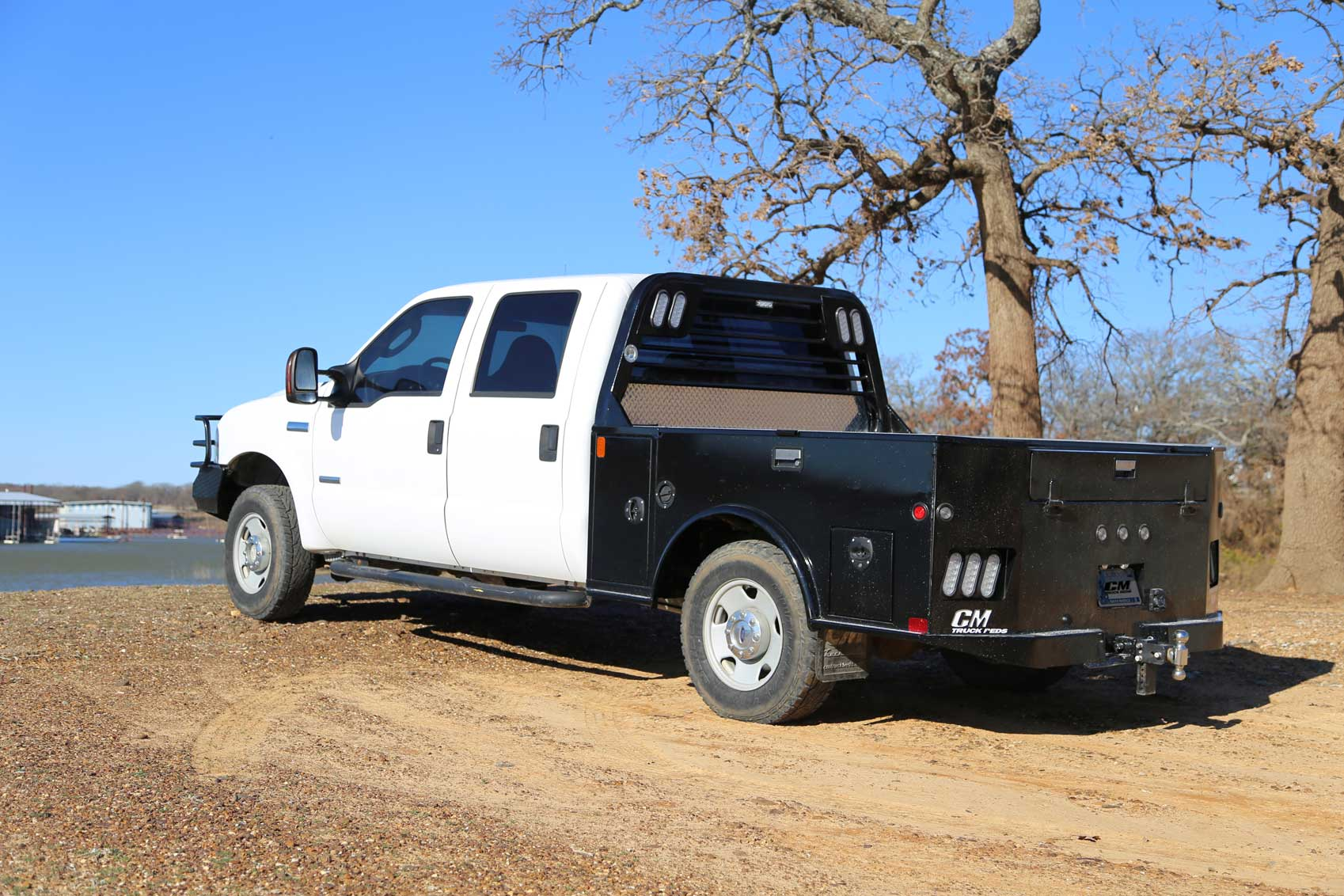 TM Deluxe towing-style flatbed next to trees with rear toolbox and gooseneck positions on farm